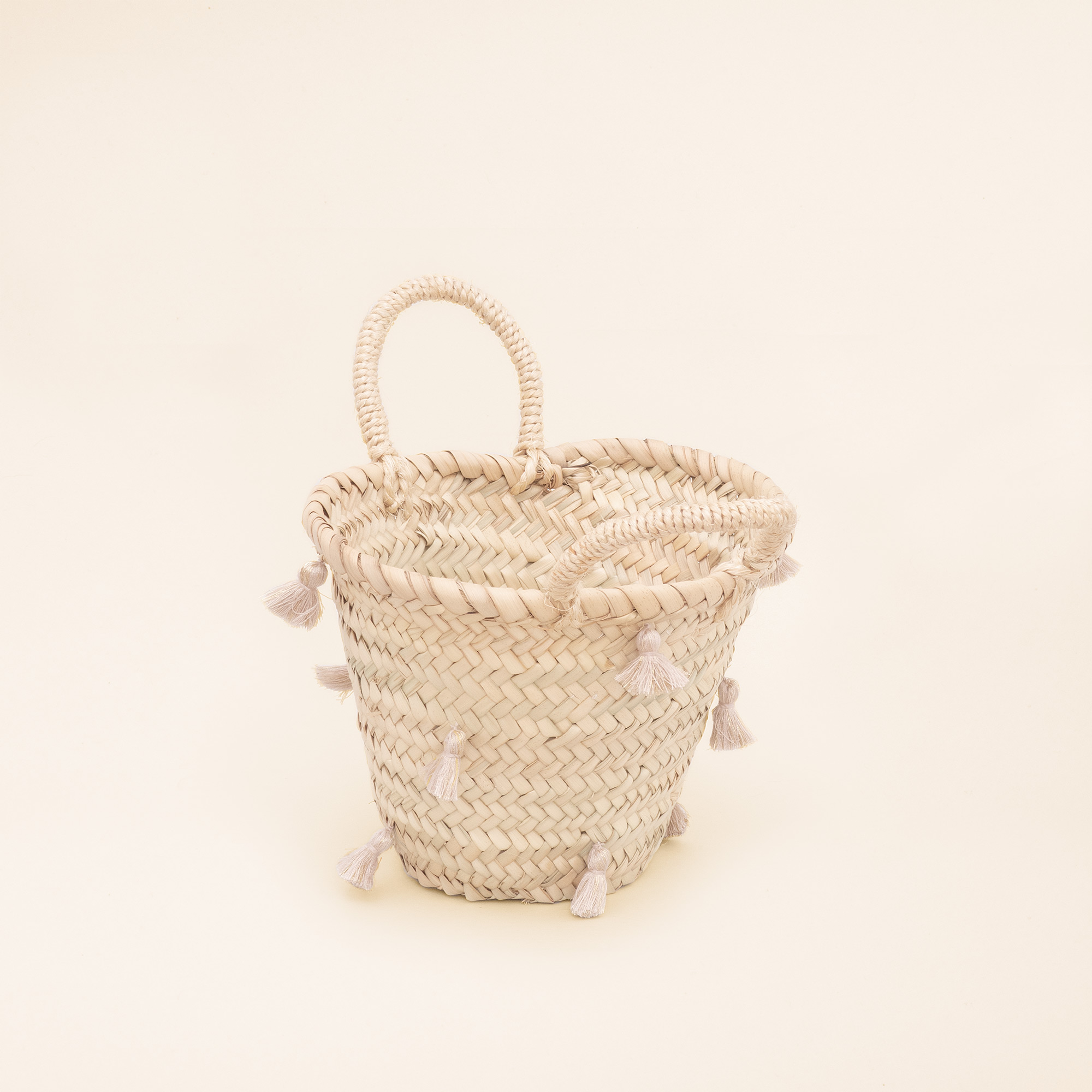 Woven basket with pompons